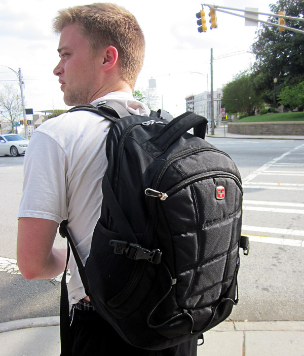 Standard Victorinox backpack, 20-25 pounds with textbooks and a laptop. A hip belt of some kind would both mitigate its pendulous action and prevent that from drawing his shirt's back up.